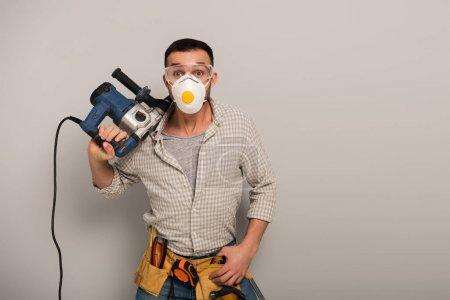 Photo pour Une travailleuse manuelle affective dans un masque de sécurité avec ceinture à outils tenant une perceuse électrique sur gris - image libre de droit