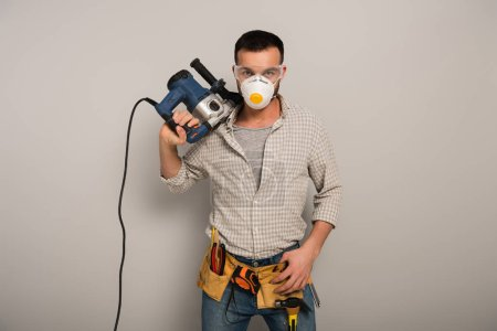 Photo pour Confident manual worker in safety mask holding electric drill on grey - image libre de droit