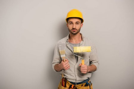 Photo pour Male manual worker in hardhat holding paint roller and brush on grey - image libre de droit