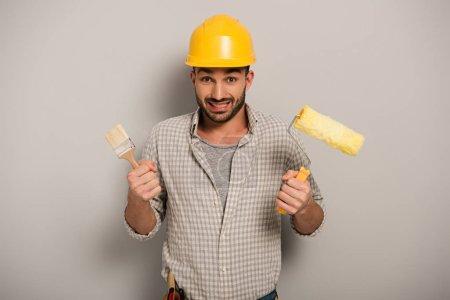 Photo pour Manœuvre confuse en casque de sécurité tenant le rouleau à peindre et le pinceau sur le gris - image libre de droit