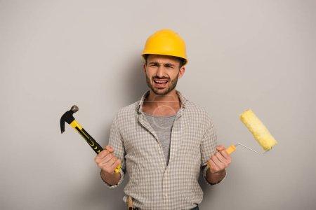 Photo pour Travailleur manuel stressé en casque de sécurité tenant la peinture rouleau et marteau sur gris - image libre de droit