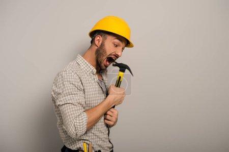 Photo pour Réparateur émotionnel en casque jaune mordant marteau sur gris - image libre de droit
