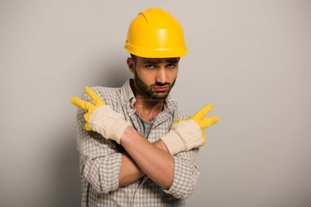 Photo for Condescending workman in yellow helmet and gloves gesturing on grey - Royalty Free Image