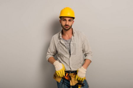 confident worker in helmet and gloves with tool belt on grey