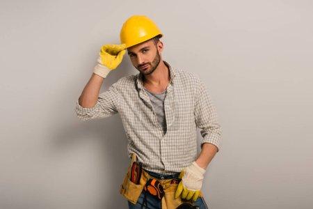 Photo pour Réparateur confiant dans le casque et les gants avec ceinture à outils sur gris - image libre de droit