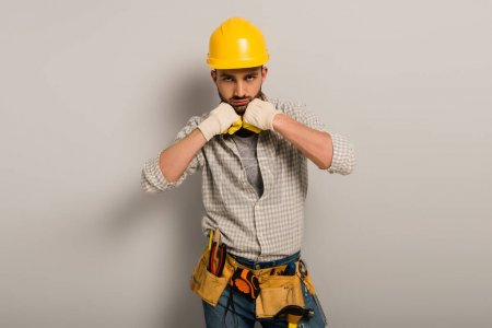 Photo pour Handsome workman in hardhat and gloves with tool belt on grey - image libre de droit