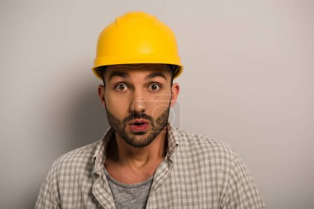 Photo for Handsome shocked manual worker in yellow hardhat on grey - Royalty Free Image