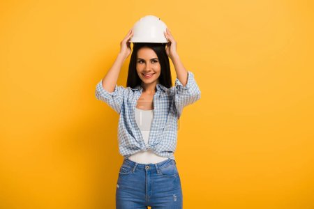 Photo pour Beautiful smiling female manual worker wearing helmet on yellow - image libre de droit