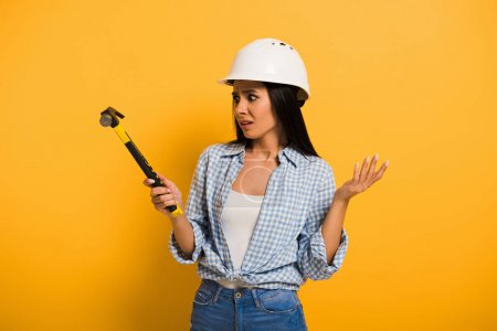 Photo pour Confused female worker in helmet holding hammer on yellow - image libre de droit
