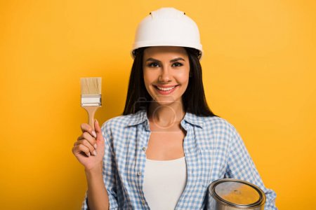 Photo for Smiling workwoman in helmet holding paint can and brush on yellow - Royalty Free Image