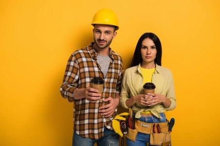 Photo pour Des ouvriers professionnels tenant des tasses avec du café pour aller en jaune - image libre de droit