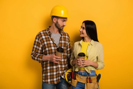 Photo for Smiling manual workers with coffee to go looking at each other on yellow - Royalty Free Image