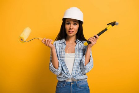 frustrated workwoman in helmet holding hammer and paint roller on yellow