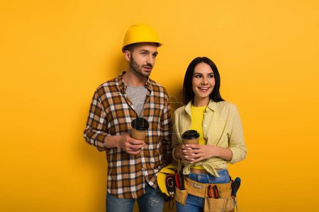 Photo for Smiling manual workers holding coffee to go on yellow - Royalty Free Image