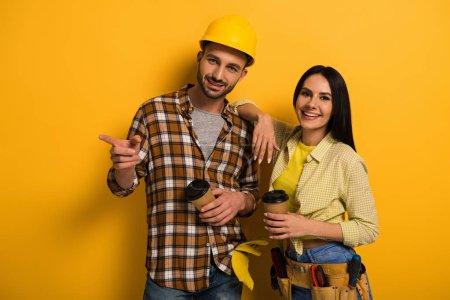 Photo pour Ouvriers professionnels avec du café pour aller pointant sur jaune - image libre de droit