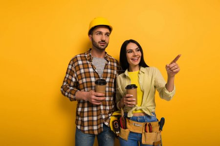 Photo for Smiling manual workers with coffee to go pointing on yellow - Royalty Free Image