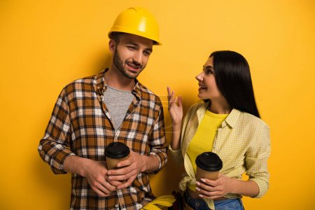 Photo for Positive manual workers talking and holding cups with coffee to go on yellow - Royalty Free Image