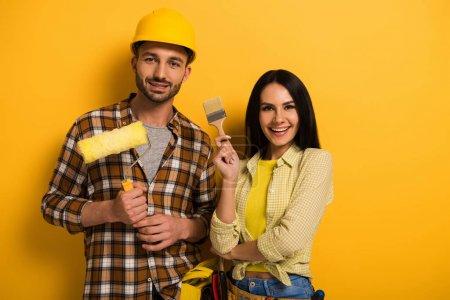 Photo pour Travailleurs manuels heureux tenant le rouleau à peindre et le pinceau sur jaune - image libre de droit