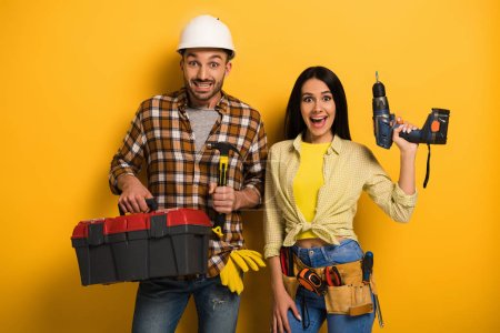 excited handywoman and handyman holding toolbox and electric drill on yellow