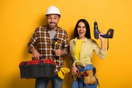 Photo pour Des travailleurs manuels excités tenant une boîte à outils et une perceuse électrique en jaune - image libre de droit