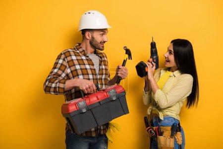 Glückliche Handarbeiter mit Werkzeugkiste und Elektrobohrer auf gelb