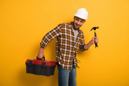 Photo pour Smiling worker in hardhat holding toolbox and hammer on yellow - image libre de droit