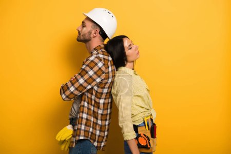 Photo for Tired manual workers standing back to back on yellow - Royalty Free Image