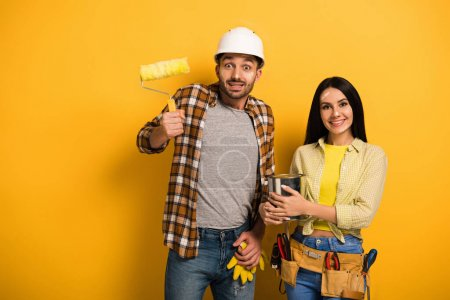 Photo for Emotional manual workers with paint roller and paint can on yellow - Royalty Free Image