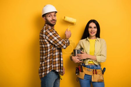 Photo for Smiling manual workers with paint roller and paint can on yellow - Royalty Free Image