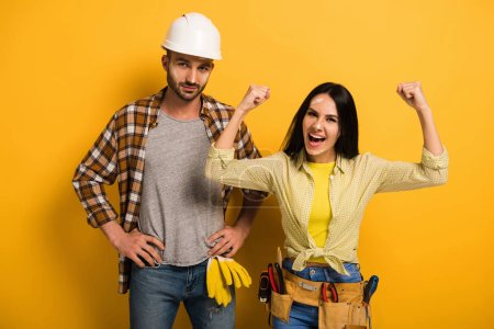 Photo for Successful excited female manual worker with hands up near coworker on yellow - Royalty Free Image
