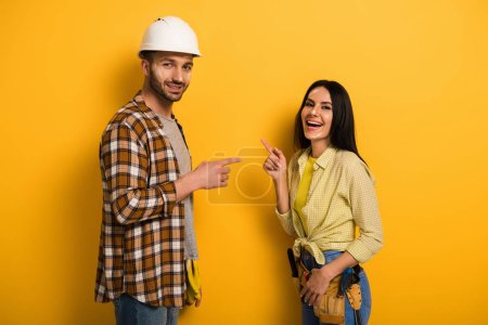 Photo for Laughing manual workers pointing at each other on yellow - Royalty Free Image