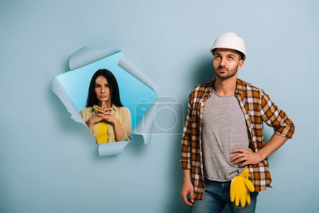 Photo for Thoughtful workman in helmet and woman in torn paper, isolated on blue - Royalty Free Image