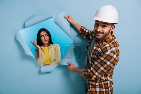 Photo for Workman in helmet and frustrated woman in torn paper, isolated on blue - Royalty Free Image