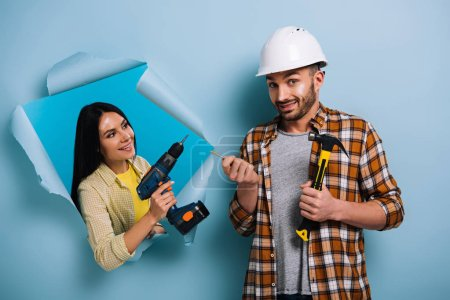 emotional workman with hammer and woman with electric drill in torn paper, isolated on blue