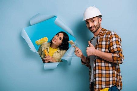 Photo pour Travailleur souriant avec pinceau montrant pouce vers le haut et femme avec rouleau de peinture en papier déchiré, isolé sur bleu - image libre de droit