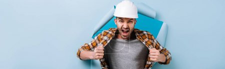 Photo for Panoramic shot of aggressive foreman in shouting in torn paper, isolated on blue - Royalty Free Image