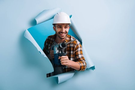 Photo pour Homme à tout faire souriant dans un casque tenant une perceuse électrique dans du papier déchiré, isolé en bleu - image libre de droit