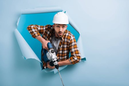 Photo pour Surprised manual worker in helmet holding electric drill in torn paper, isolated on blue - image libre de droit