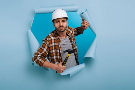 Photo for Angry repairman in helmet holding hammer in torn paper, isolated on blue - Royalty Free Image