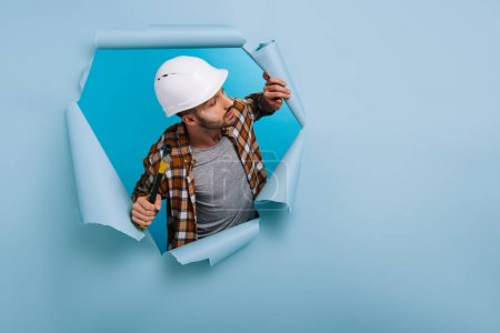 Photo for Aggressive worker in helmet holding hammer in torn paper, isolated on blue - Royalty Free Image