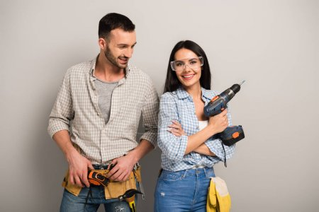 Photo for Protective manual workers holding electric drill on grey - Royalty Free Image