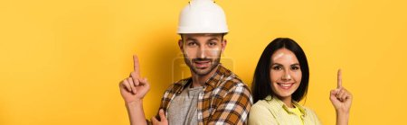 Photo for Panoramic shot of cheerful manual workers having idea and pointing up on yellow - Royalty Free Image