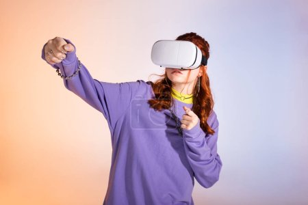Photo for Emotional teen girl gesturing and using virtual reality headset, on purple and beige - Royalty Free Image