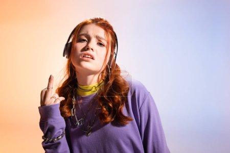 Photo pour Une adolescente en colère écoute de la musique avec des écouteurs et montre le majeur, violette et beige - image libre de droit