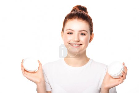 Photo for Positive teenager with perfect skin holding plastic container with cosmetic cream, isolated on white - Royalty Free Image