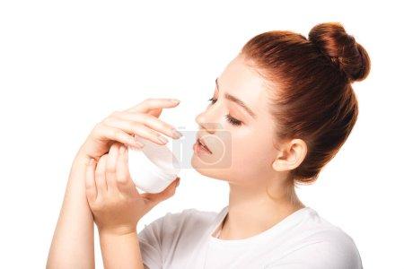 Photo pour Séduisante adolescente avec peau parfaite tenant récipient en plastique avec crème cosmétique, isolé sur blanc - image libre de droit