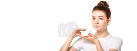 panoramic shot of beautiful teen girl with perfect skin holding plastic container with cosmetic cream, isolated on white