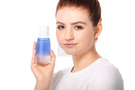Photo pour Belle adolescente souriante avec une peau propre tenant bouteille avec démaquillant bleu, isolé sur blanc - image libre de droit