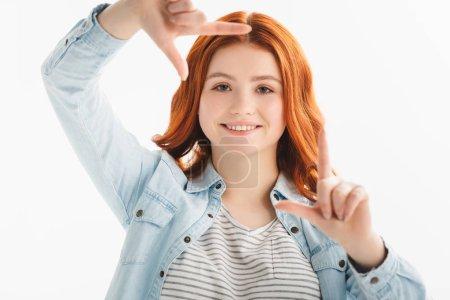 Photo pour Rousse souriante adolescente montrant un cadre fait de mains, isolée sur blanc - image libre de droit