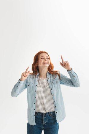 Photo pour Heureux émotionnel rousse femme adolescent pointant vers le haut, isolé sur blanc - image libre de droit